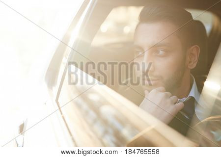 Sunlit portrait of handsome Middle-Eastern businessman riding in backseat of car  and looking out of window watching city streets