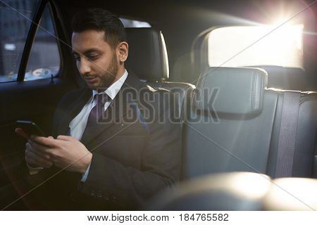 Portrait of handsome Middle-Eastern businessman using smartphone on backseat inside expensive car