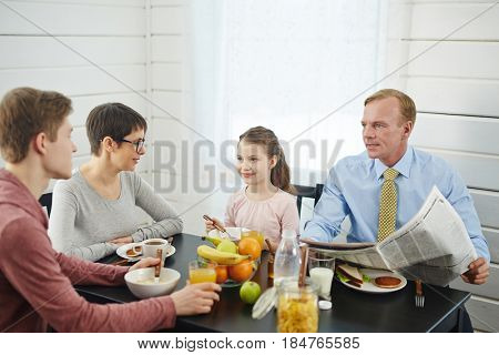 Peaceful breakfast in bosom of family: red-haired father with newspaper in hands talking to his teenage son, little daughter and her short-haired mother enjoying delicious food