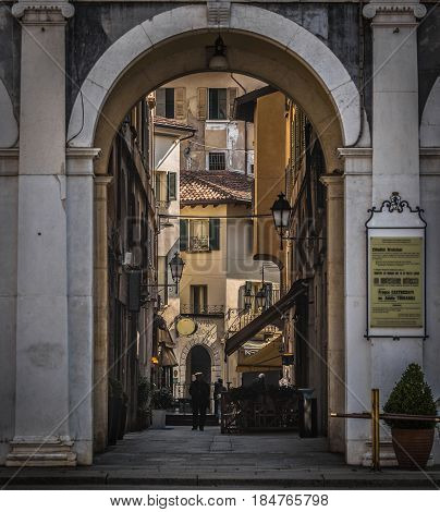 Old street in Brescia, view through the arch in the center of the city
