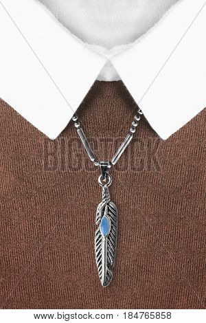 Silver feather shaped pendant with turquoise over brown pullover with white collar closeup