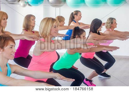 female keep fit exercising stretching class