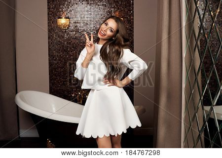Sexy beautiful joyous and crazy girl in white top and skirt standing in luxury interior with mirror wall and bath showing tongue and peace sign with fingers