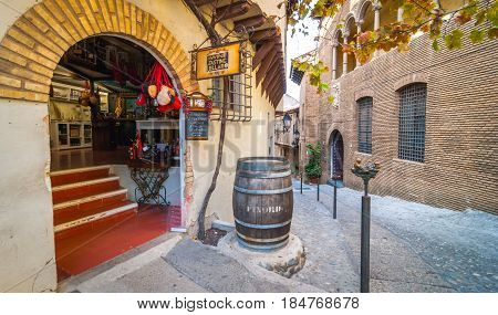 Barcelona, Spain - Nov 2nd, 2013:  Tourism in Barceloneta - small town on the interior of Barcelona.  Find charming cafes, shops, & here, a delightful wine store with brick arch entry in narrow alley