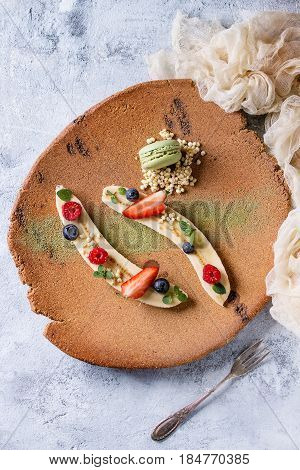 Food plating dessert organic banana with fresh berries, mint, puffed rice and macaroon biscuit served with green tea matcha powder on terracotta plate. Gray texture background, textile gauze. Flat lay