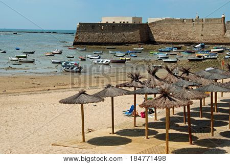 CADIZ, SPAIN - SEPTEMBER 8, 2008 - Parasols on La Caleta beach with the harbour and Castle to the rear Cadiz Cadiz Province Andalusia Spain Western Europe, September 8, 2008.
