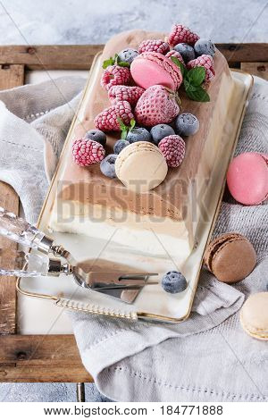 Three layers vanilla, coffee and chocolate ice cream cake, served with frozen berries and macaroons biscuits on rectangular white plate, textile napkin over gray texture background.