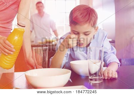 Midsection of woman with juice bottle standing by son having breakfast with man in background