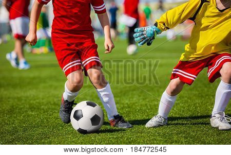 Boys with Soccer Ball. Children Playing Soccer Football Match. Youth Soccer Forward and Goalkeeper Duel. Football soccer game. Players footballers running and playing football match