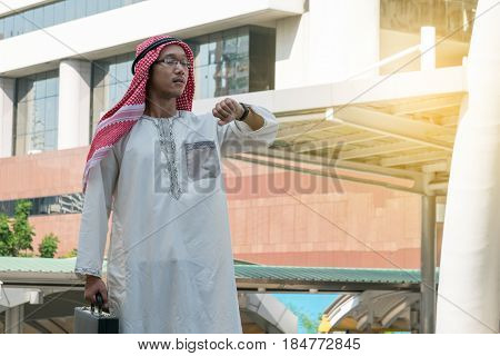 Arab business man checking the time on her watch.