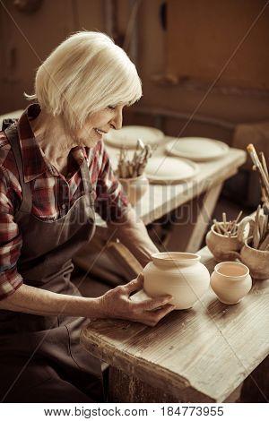 Female Potter Sitting At Table And Examining Ceramic Bowl At Workshop
