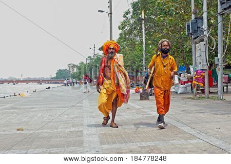 INDIA, HARIDWAR - APRIL 24, 2017: Two sadhus walking along the river Ganges in Haridwar on 24th of april 2017