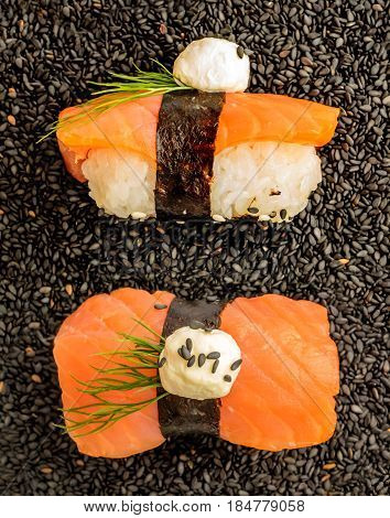 Nigiri Sushi With Salmon And Seaweed Nori On Dark Background