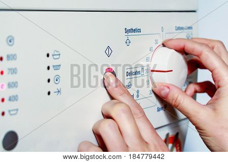 Closeup of female hand pressing start button and adjusting the wash settings with a knob on white modern washing machine