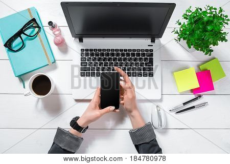 Flat lay, top view office table desk. Workspace with girl's hands, laptop, green flower in a pot, mint diary, coffee mug on white background.
