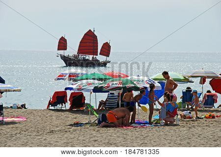 TORREMOLINOS, SPAIN - SEPTEMBER 3, 2008 - Tourists relaxing on the beach with a junk ship out to sea Torremolinos Malaga Province Andalusia Spain Western Europe, September 3, 2008.