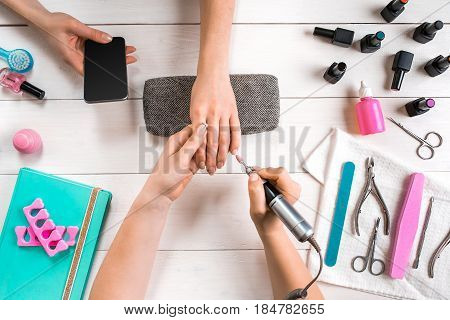 Manicure for the client. Close-up of the hands of a manicurist and client on a wooden background. Nail care. Manicure set and nail polish.