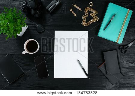 Flat lay, top view office table desk frame. Workspace with clean sheet of paper, mint diary and mobile device on dark background. Copy space