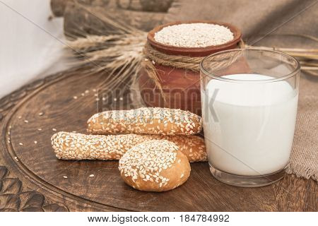 Milk in glass, bread sticks, buns on wooden table. Sesame milk in glass. White sesame seeds in clay pot on a wooden table. Healthy breakfast and beverage. Calcium-rich Diet. Natural organic products. Horizontal photo without people for catalog, menu, bill