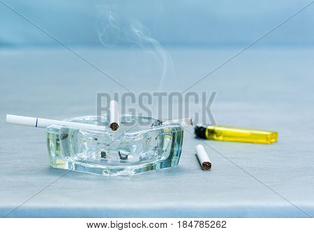 White cigarettes and clear ashtray on leather background