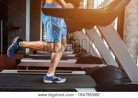 Legs running on the treadmill close up. A muscular man in yellow sneakers and blue shorts running down the treadmill in the gym. Motion blur