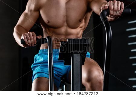 Intense cardio workout. View close-up part of young man in sports shorts cycling at gym. Muscular man. Part of the body
