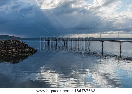 Rays of sunlight break through the clouds over the pier at Des Moines Washington.