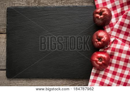 Ripe red apples on wooden board with red checkered napkin around and copy space on black slate dish.