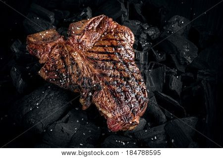 Grilling a tasty tender marinated t-bone steak on a coals. Close up view. Copy space