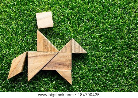 Wooden tangram puzzle in man on the horse shape start up or discover concept