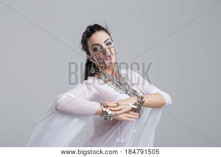 Sexy arabic belly dancer dancing on grey background portrait