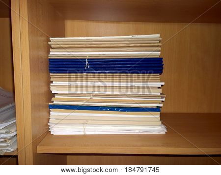 Accounting magazines stacked in a stack on a cabinet of light brown color
