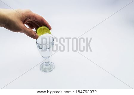 Tequila shot with a female squeezing a lime into it