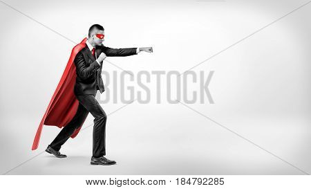 A businessman in a flowing red superhero cape and a mask throwing punches at an invisible enemy on white background. Business and rivalry. Overcoming difficulties. Fight for success.