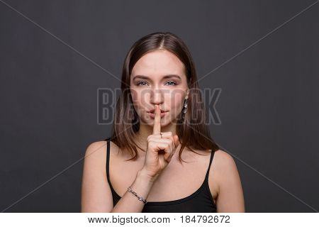 Secret. Young woman put finger on lips, hush sign, keep silence. Girl on dark background