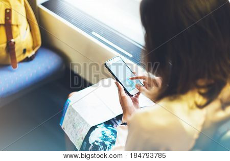 Enjoying travel. Young pretty woman traveling by train sitting near the window using smartphone and looking map. Tourist texting online message and plan route of railway railroad transport concept mock up