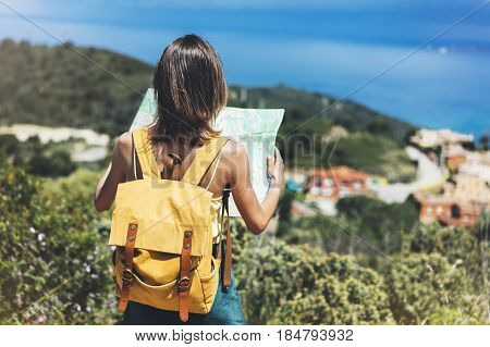 Hipster tourist hold and look map on trip lifestyle concept adventure traveler with backpack on background mountain and blue sea landscape horizon young girl hiker pointing hands on trekking plan