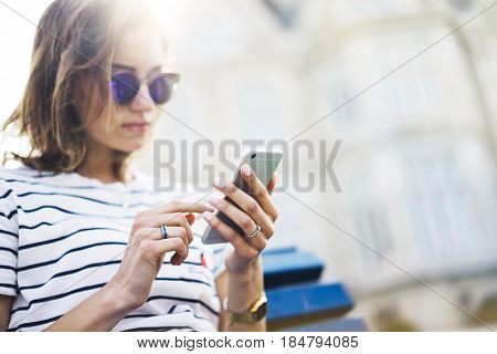 Hipster texting message on smartphone or technology mockup of blank screen. Girl using cellphone on building castle background close. Tourist female hands holding gadget on blurred summer backdrop