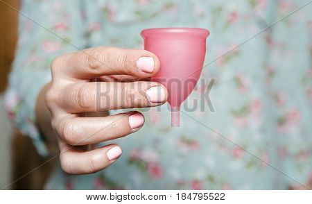 Woman hand holding pink menstrual cup. Modern female intimate hygiene concept.