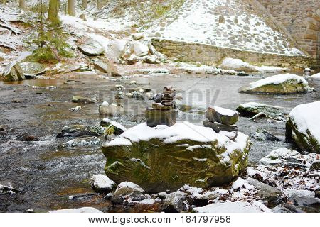stone cairn by the river in wintertime