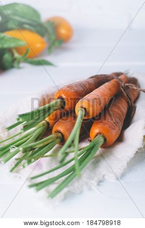 Bunch of young carrots with green tops on white wooden vintage table healthy food on mock up background top view diet and vegetarian orange vegetable; vitamin agriculture concept