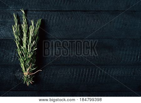 Green rosemary bunch on black vintage wooden background close up top view natural organic aromatic food on kitchen table vegan spice on mock up seasoning herb on cooking process copy space