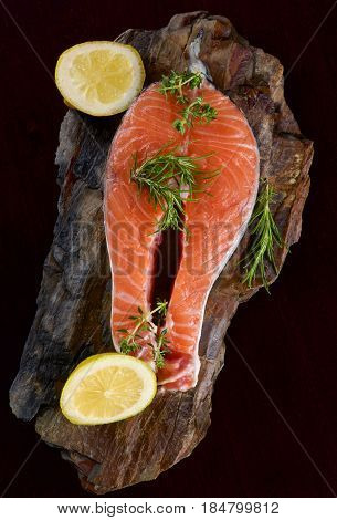 Raw Salmon Steak with Slices of Lemon and Rosemary on Shale Stone Board closeup on Dark Wooden background. Top View