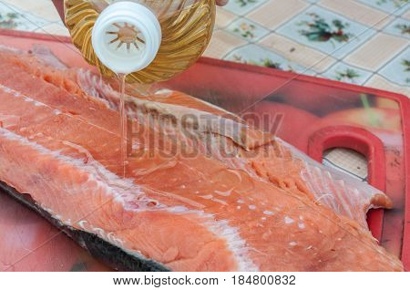 Raw red fish fillets are sprinkled with clear oil