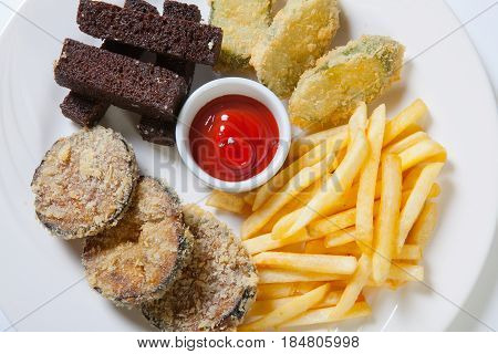 Fresh Beer Snacks Assortment On A White Plate. French Fries, Croutons And Eggplant
