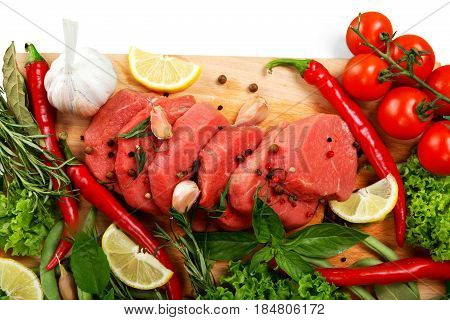 fresh meat - fresh steaks on a yellow mat, fresh herbs and vegetables isolated on white background