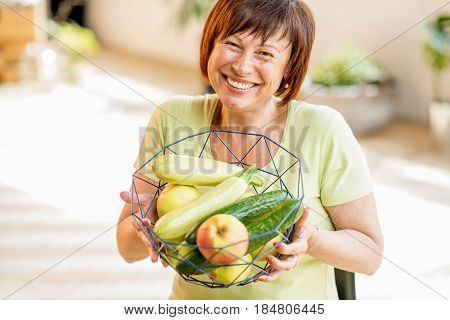 Smiling older woman holding fruits and vegetables indoors