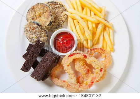 Fresh Beer Snacks Assortment On A White Plate. French Fries, Croutons And Zucchini And Sweet Pepper