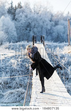 Winter landscape, girl with blond hair and short hairstyle in a black fur coat on a background river under the ice and tree branches covered with white frost. Pedestrian suspension bridge
