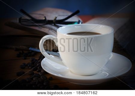 Hot coffee in a white cup near the book